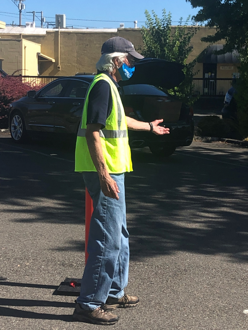 George Coulborn directs traffic as more than 140 seniors arrive to collect their Senior Picnic lunches.